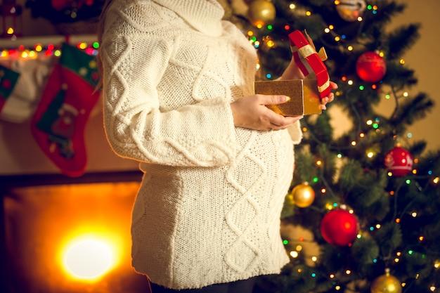 크리스마스 선물 상자와 함께 포즈를 취하는 임산부의 몸매 사진