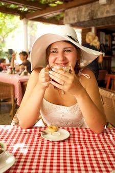 화창한 아침에 카페에서 차를 마시는 젊은 여성의 몸매 사진