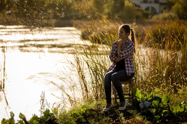 호수 석양에 앉아 젊은 여자의 몸매 사진