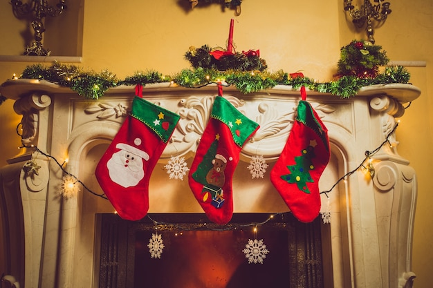 Toned photo of three red christmas socks hanging on fireplace at house