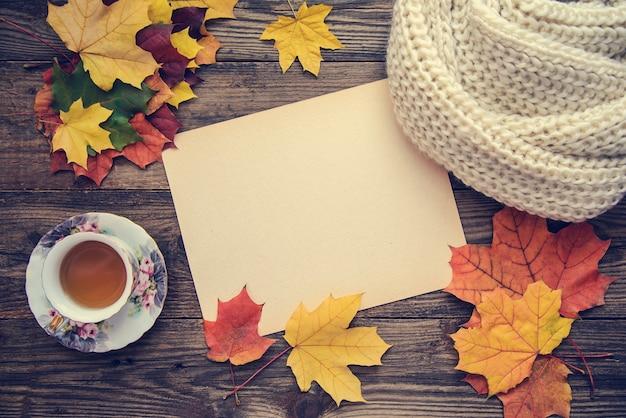 Тонированное изображение с осенними листьями, чашкой чая и блокнотом