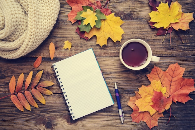Toned picture with autumn leaves, a cup of tea and a notebook