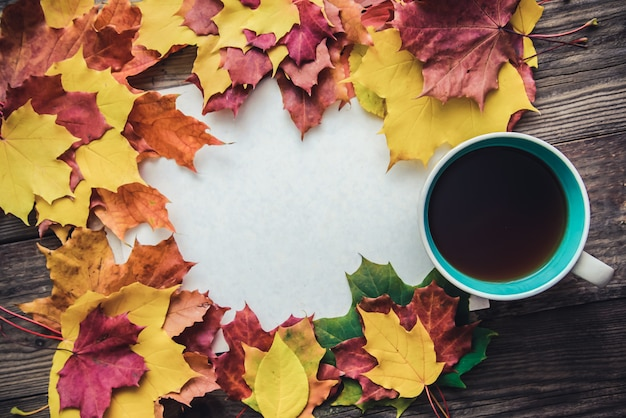 Toned picture with orange and yellow autumn leaves, cup of tea and sheet of paper on wooden background with copy space