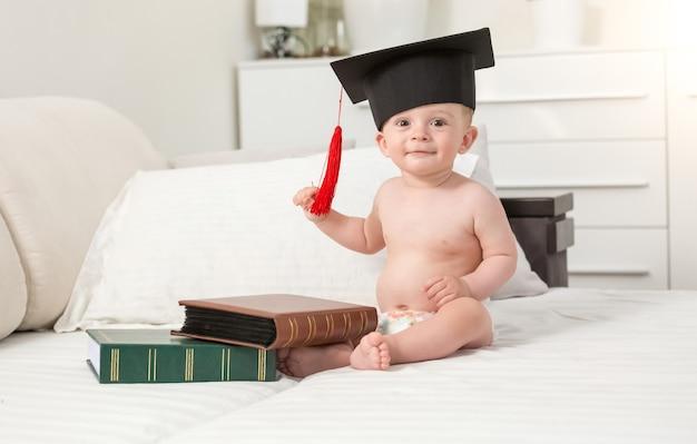 소파에 검은 졸업 모자 좌석에 쾌활한 아기 소년의 톤의 초상화