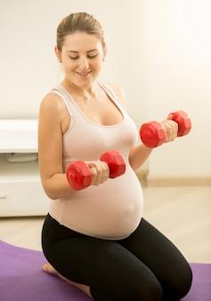 マットの上に座ってダンベルを保持している妊婦のトーンの肖像画