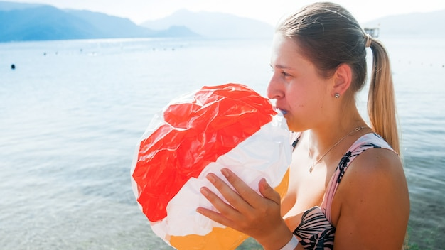 바다에 풍선 비치 볼에 공기를 불고 웃는 젊은 어머니의 톤된 초상화.