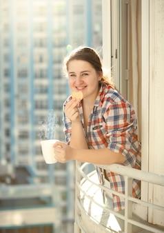 Тонированный портрет женщины, едящей печенье и пьющей кофе на балконе