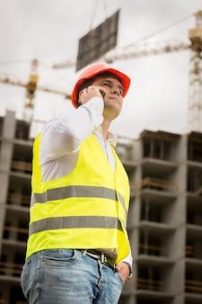 건설 현장에 전화로 얘기하는 젊은 건설 엔지니어의 톤된 초상화.