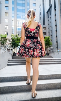 Toned rear view photo of sexy young woman in short dress and ballet flats walking up the stone stairs next to high modern building and skyscrapers.