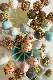 Toned top view shot of colorful cake pops against white wooden background