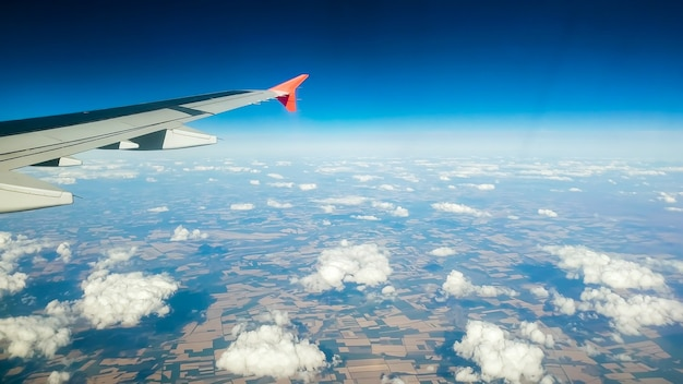 Toned view of airplane wing flying above clouds and land.