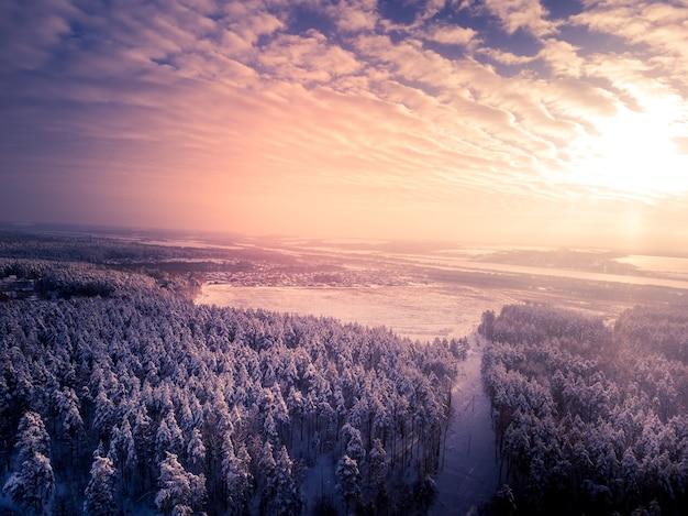 흐린 하늘과 태양 주위 필드 겨울 숲 근처 톤된 마을 공중 보기