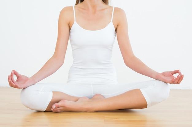 Toned woman in lotus pose at fitness studio