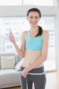 Toned woman measuring waist while gesturing thumbs up