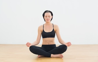 Toned woman sitting in lotus pose with eyes closed