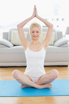 Toned woman sitting with joined hands over head at fitness studio