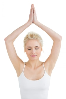 Toned woman with joined hands and eyes closed