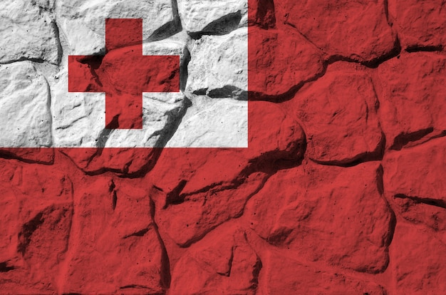Tonga flag depicted in paint colors on old stone wall closeup. textured banner on rock wall background