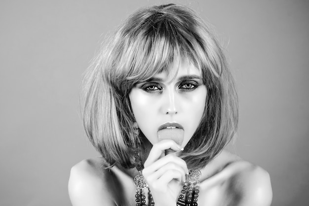 Tongue. girl with bright artificial hair in ethnic jewelry. black white.