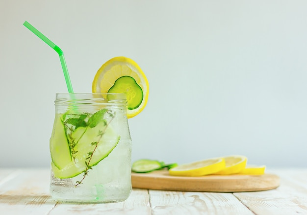 Tonic drink from cucumbers and lemon in a glass jar on a table with a copy space. homemade summer refreshing beverage.