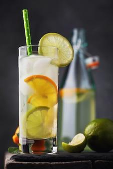 Тонизирующий напиток с лимоном и лаймом в прозрачном стакане с открытой бутылкой на деревянном столе