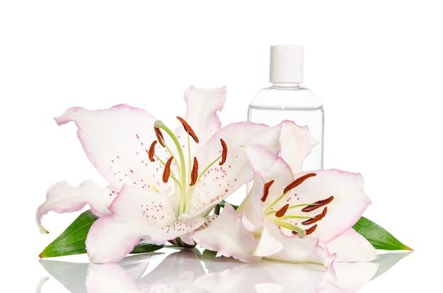 白い背景の上のユリの花とスキンケアのための強壮剤