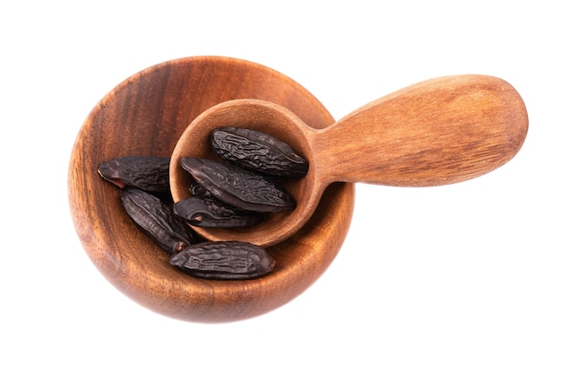Tonka beans in wooden bowl and spoon, isolated