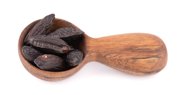 Tonka beans in wooden spoon, isolated on white
