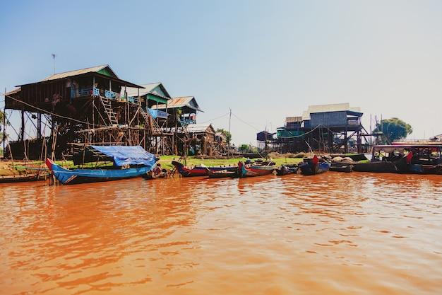 Озеро тонлесап. плавучая рыбацкая деревня кампонг пхлюк в сезон засухи. дома на сваях, люди и лодки. бедная страна. жизнь и работа жителей камбоджи на воде, недалеко от сиемреапа, камбоджа