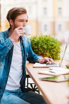 オフィスに座るには美しすぎる日。コーヒーを飲み、ラップトップに取り組んでいるハンサムな若い男