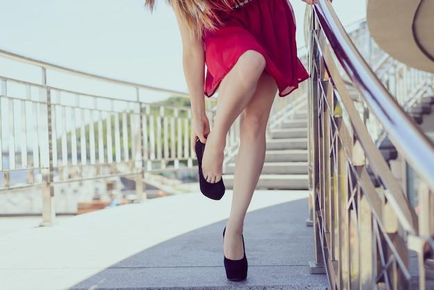 너무 큰 작은 빨간색 짧은 옷은 고급스러운 우아한 개념을 옷을 벗습니다. 피곤한 섹시한 여성이 신발을 벗고 편안한 바쁜 날 파티 축하 시간 개념을 벗고 있는 사진을 클로즈업