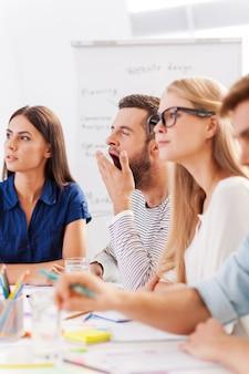 Слишком скучная презентация. группа молодых деловых людей в элегантной повседневной одежде, скучающей, сидя вместе за столом и глядя в сторону