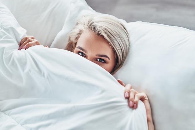 目覚めるのが面倒。魅力的な若い女性の顔の半分を毛布で覆い、自宅のベッドに横たわっているときにカメラを見ている上面図