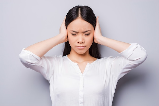 Too loud sound. beautiful young asian women covering ears with hands and keeping eyes closed while standing against grey background