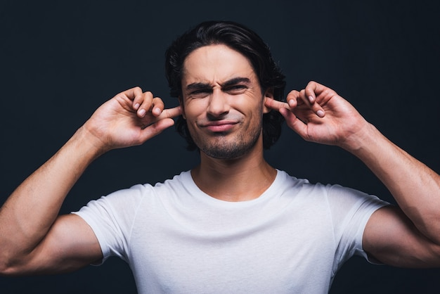 Too loud sound. portrait of young man expressing negativity and covering ears by hands while standing