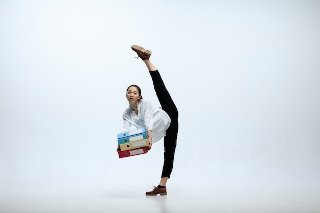 Слишком много дел за день. серьезная женщина, работающая в офисе, прыгает и танцует в повседневной одежде или костюме, изолированном на белом фоне студии. бизнес, запуск, рабочая концепция открытого пространства.