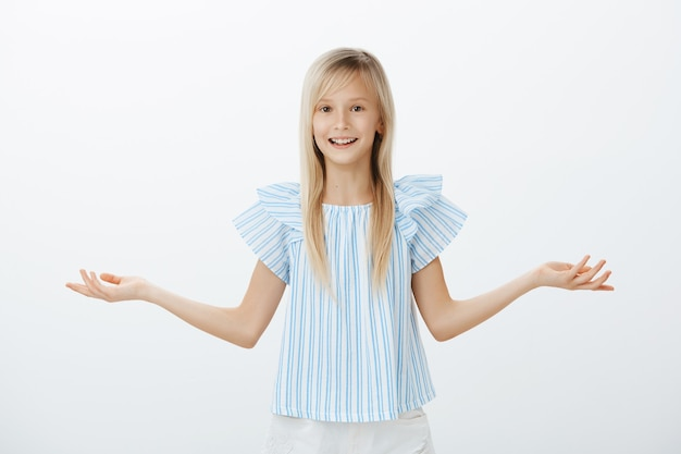 Too many choices for one kid. portrait of clueless confused attractive young blond girl in blue blouse, spreading palm and weighing options or shrugging, being questioned and unaware over gray wall