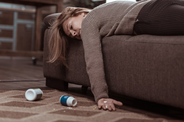 Too many pills. blonde-haired mature family woman falling asleep after taking too many pills