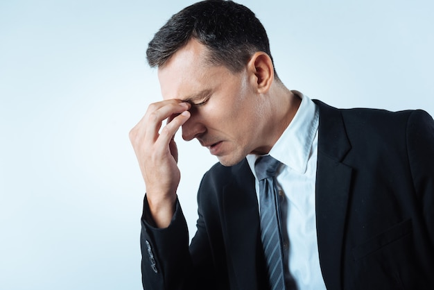 問題が多すぎます。彼の鼻の橋を保持し、彼の問題について考えている間不幸を感じている素敵な元気のないハンサムな男