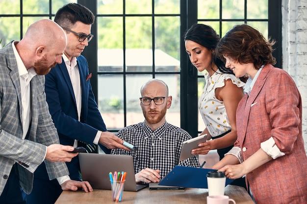 동료들에게 둘러싸인 젊은 사업가의 너무 많은 작업 선택적 초점, 각각 프로젝트 제안, 승인 또는 서명 요청