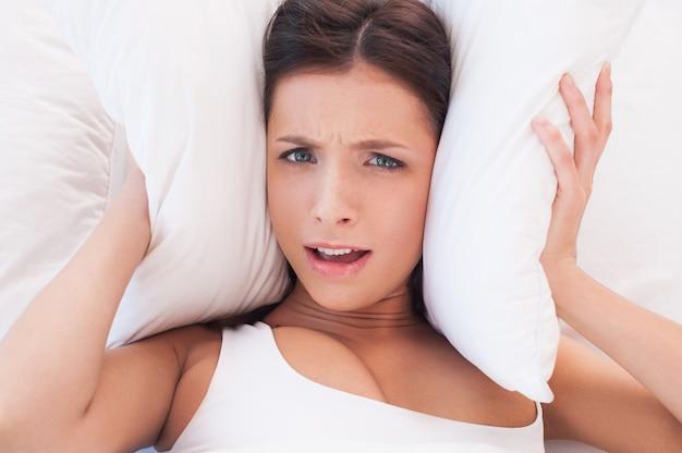 ノイズが多すぎます。騒音のため枕で耳を覆う美しい若い女性