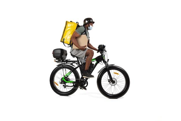 注文が多すぎます。検疫中の無連絡配達サービス。男は、ヘルメットとフェイスマスクを着用して、隔離中に食べ物を届けます。白い壁に隔離された自転車で食べ物を取る。安全性。急いで。