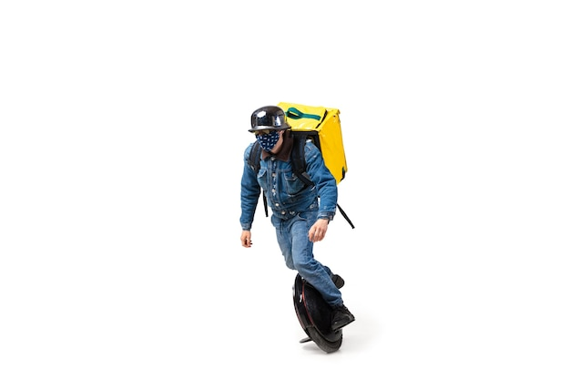 注文が多すぎます。検疫中の無接触配達サービス。男は白で隔離の手袋とフェイスマスクを身に着けている食品を提供します。白い背景で隔離の一輪車でピザを取る。安全性。