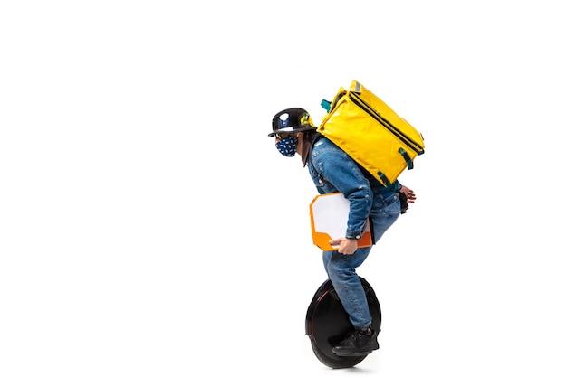 注文が多すぎます。検疫中の無連絡配達サービス。男は白で隔離の手袋とフェイスマスクを身に着けている食品を提供します。白い背景で隔離の一輪車でピザを取る。安全性。