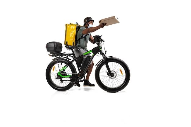 注文が多すぎます。検疫中の非接触配送サービス。男性は隔離中にヘルメットとフェイスマスクを着用して食べ物を配達します白い壁に隔離された自転車で食べ物を取ります。安全性。急いで。