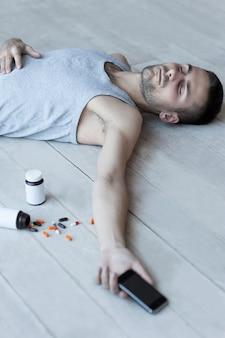 알약이 너무 많습니다. 바닥에 누워 손에 휴대전화를 들고 있는 젊은 남자, 그 근처에 약이 든 병을 들고 있는 모습