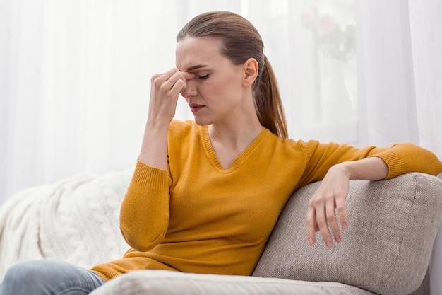 プレッシャーが強すぎる。ソファに座ってリラックスしながら鼻梁に手を置く魅力的な疲れた疲れた女性