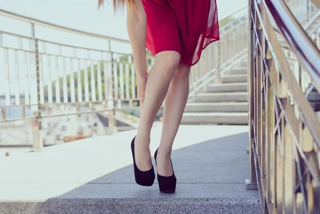 Слишком маленькие большие высокие каблуки, натирающие концепцию подставки для мозолей. низкий угол крупным планом передний фотопортрет довольно красивой несчастной грустной дамы, имеющей проблемы с ботинками, массирующими заднюю часть ног на фоне города