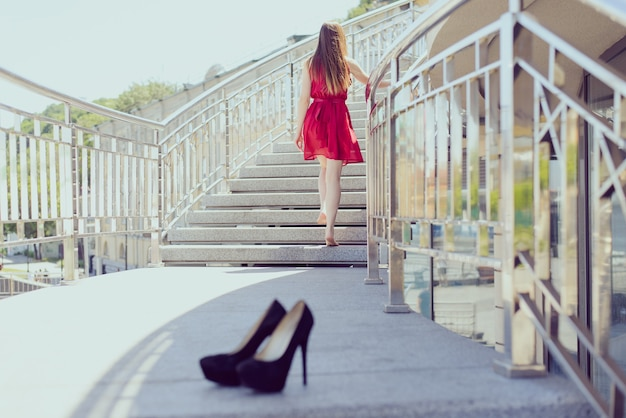 Too small discomfort cramp after work party leaving blur background concept. rear behind back close up view photo portrait of pretty lonely alone single cute student took off shoes going up the stairs