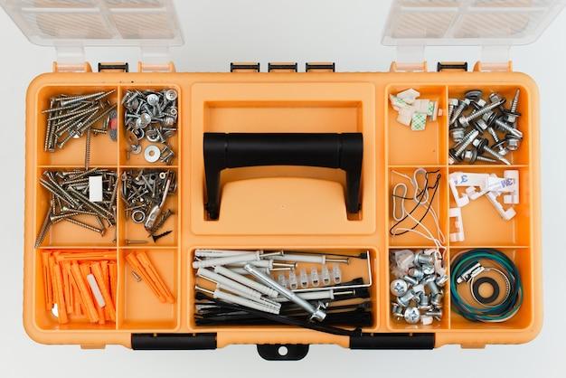 위에서 본 다양한 종류의 나사와 못이있는 도구 상자.